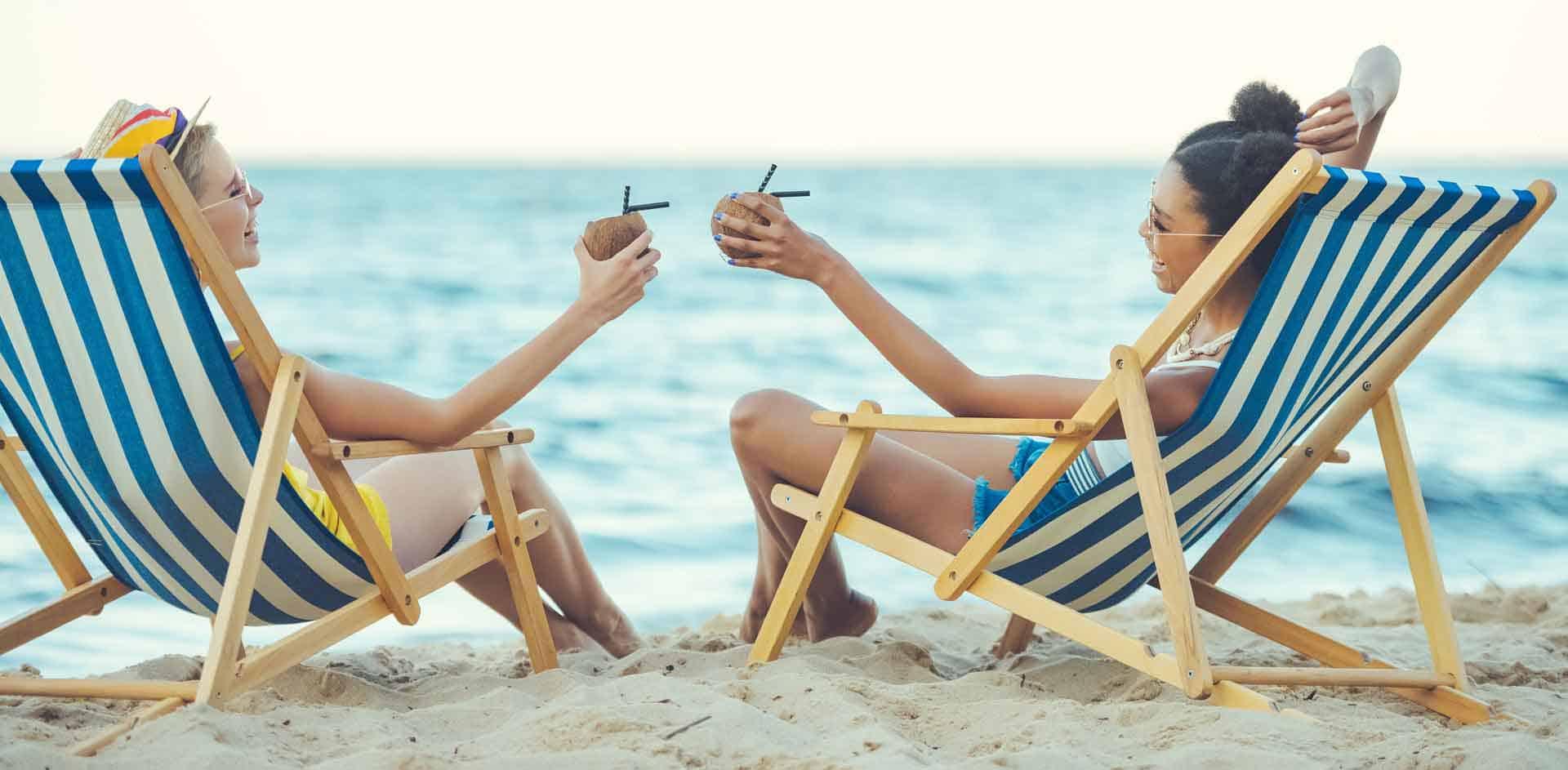 women on the beach enjoying cocktails