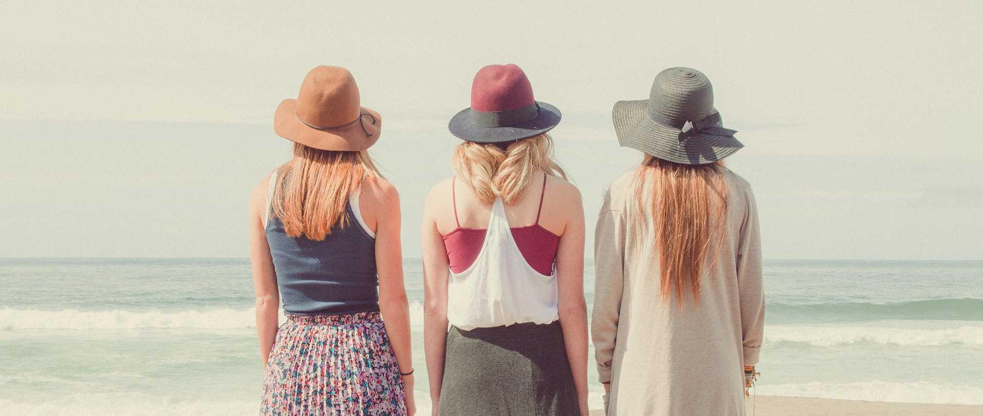 3 women on the beach facing the ocean