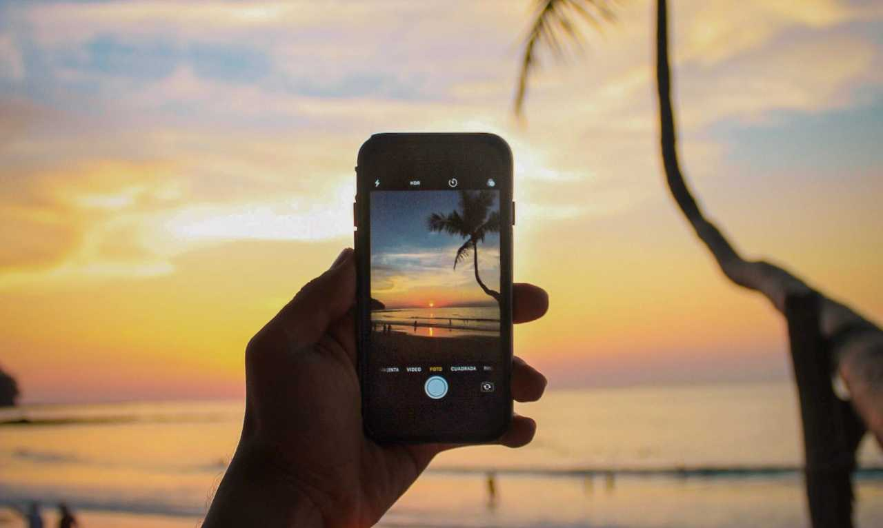 cell phone taking a picture of the sunset on a beach