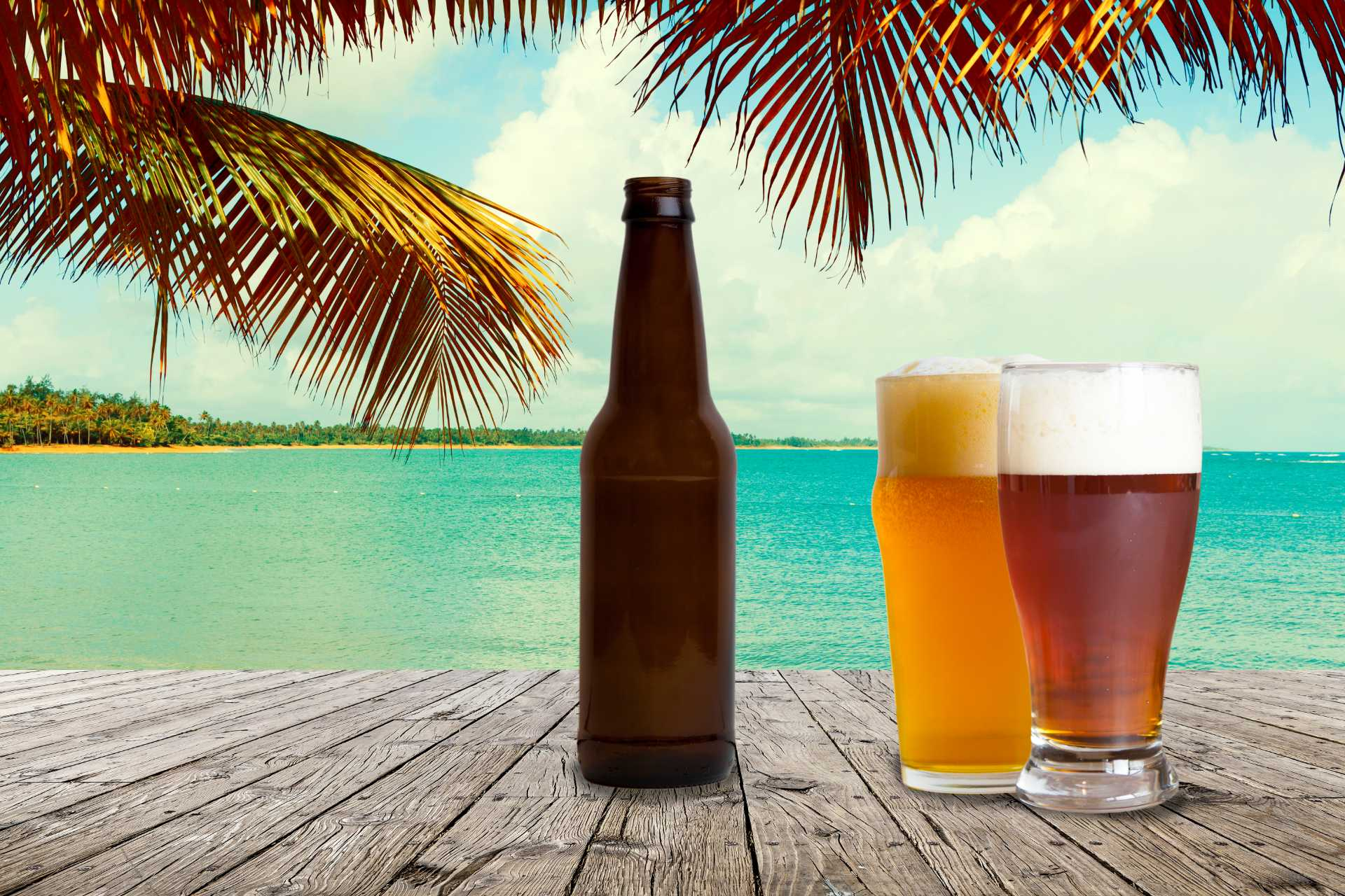 glasses and bottle of beer with beach background