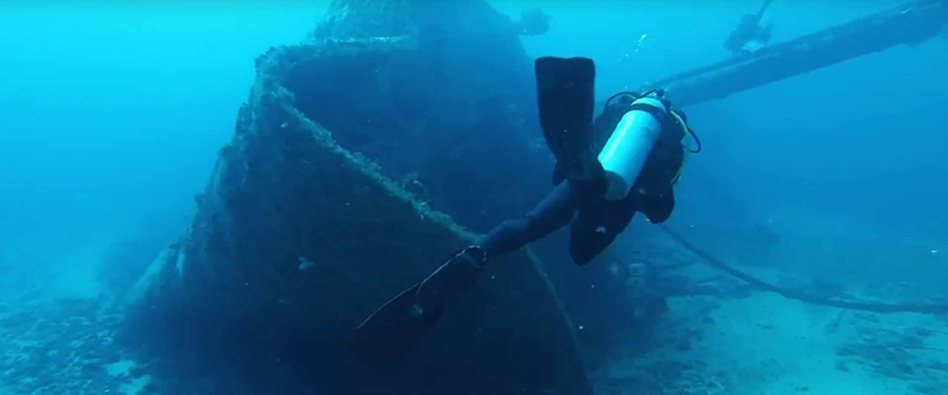 scuba diver swimming around a shipwreck in Grenada